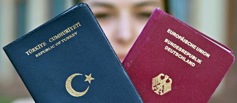 Eine Frau hält einen türkischen und einen deutschen Pass ins Bild