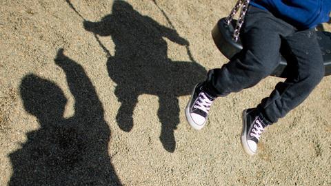 Silhouetten von einem Erwachsenen, der ein Kind schaukelt