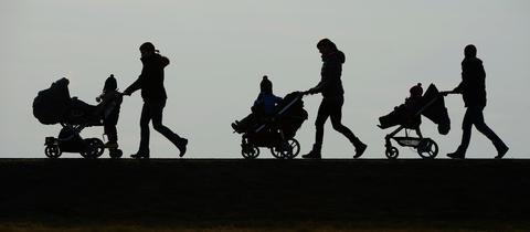 Silhouetten von Menschen die Kinderwagen schieben