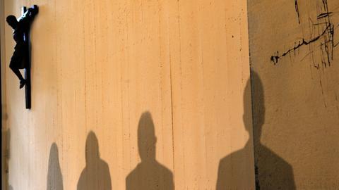 Kleriker werfen einen Schatten an die Wand mit Jesuskreuz
