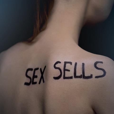 """Auf dem nackten Rücken einer Frau steht """"Sex Sells"""""""