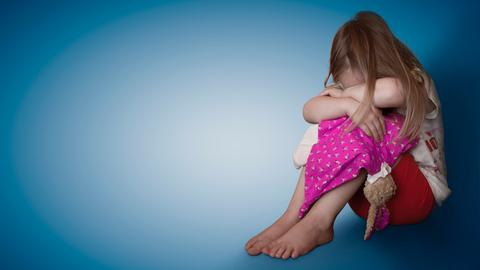 Ein Mädchen kauert mit gesenktem Kopf.