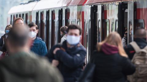 Fahrgäste mit einem Mund-Nasen-Schutz steigen an einem Bahnhof aus einer S-Bahn aus