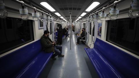 Pendler sitzen in Zeiten des Corona-Virus in einer leeren U-Bahn in Peking.