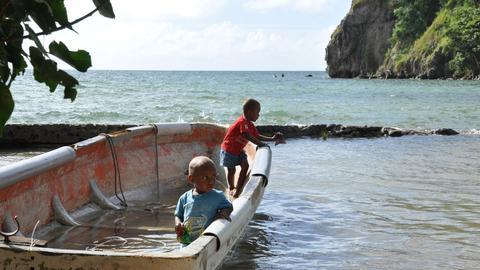 Kinder in einem Boot im Wasser vor der Mauer, die überflutet ist