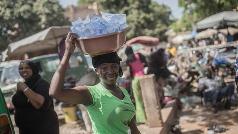 Frau in Mali trägt Korb mit Wasserbeuteln auf dem Kopf