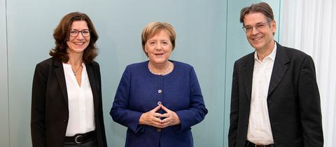 Kanzlerin Angela Merkel (m.) mit hr-iNFO-Programmleiterin Katja Marx und Hauptstadtkorrespondent Andreas Reuter