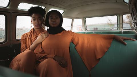 Zwei dunkelhäutige Models mit organge-farbenen Kleidern aus der Mizaan-Modekollektion