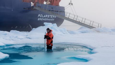 Ein Mann macht Messungen in einem Schmelztümpel auf arktischem Meereis, im Hintergrund sieht man das Schiff Polarstern