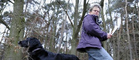 Wolfsexpertin Susanne Jokisch mit ihrem Hund im Wald