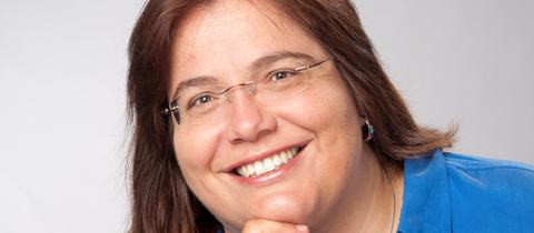 Frau mit braunen Haaren, Brille und blauem Oberteil lächelt in die Kamera
