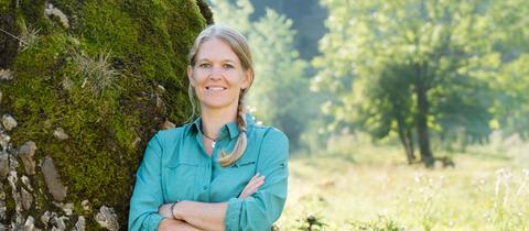 Vaude-Geschäftsführerin Antje von Dewitz lehnt im Wald an einem großen Stein.