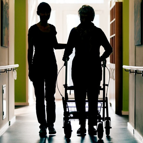 Eine Pflegekraft begleitet eine alte Frau im Pflegeheim