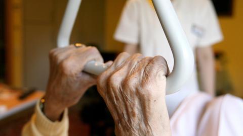 Eine Pflegehausbewohnerin in einem Seniorenzentrum hält sich am in ihrem Bett an einem Haltegriff fest.