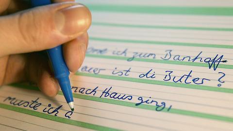 Ein Analphabet schreibt Sätze zur Übung in ein Heft