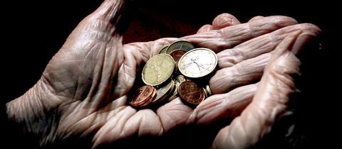 Faltige Hände halten Kleingeld