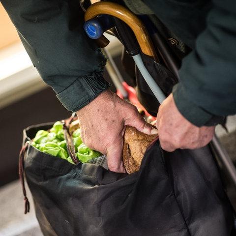 Hilfsbedürftiger Rentner packt bei der Mainzer Tafel Brot ein