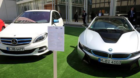 Zwei weiße Elektroautos von BMW und Mercedes