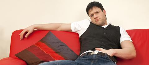 Ein Prolet sitzt, Hand in der Hose, faul auf der Couch.