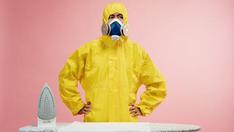 Mann mit Schutzkleidung steht vor Bügelbrett