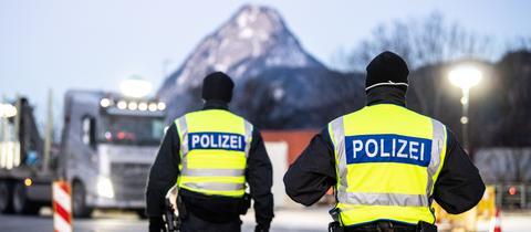 Polizisten am Grenzübergang zu Tirol. Im Hintergrund wartet ein LKW darauf, passieren zu dürfen.