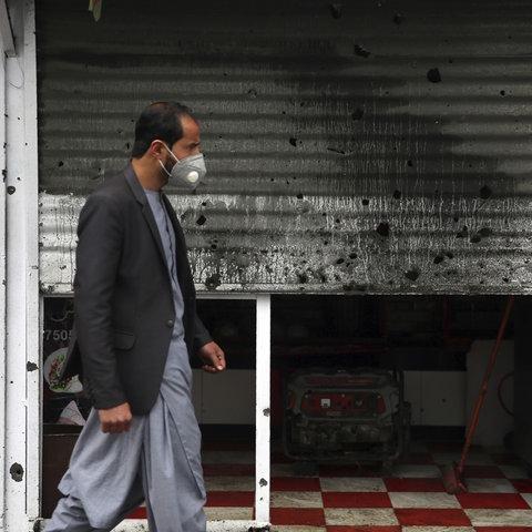 Ein Mann in Kabul trägt Maske und läuft an einem Geschäft vorbei, das durch eine Bombenexplosion beschädigt wurde.