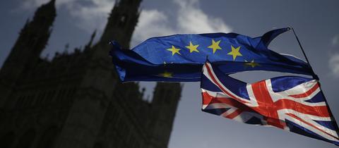 """Der britische """"Union Jack"""" und die Europa-Flagge wehen vor dem britischen Parlament gemeinsam im Wind."""