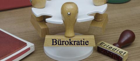 """Auf einem Stempelhalter hängt ein Stempel mit der Aufschrift """"Bürokratie"""""""