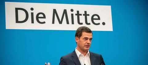 """Thüringens CDU-Vorsitzender Mike Möhring steht vor einem Plakat auf dem """"Die Mitte."""" steht"""