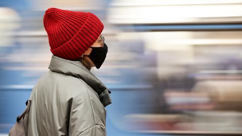 Eine Frau mit Wollmütze und Maske steht auf dem Bahngleis vor einem Zug.