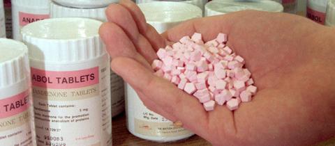 Ein Zollbeamter hält Pillen zum Muskelaufbau in der Hand.