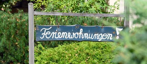 """Auf einem Wegweiser steht """"Ferienwohnungen"""""""