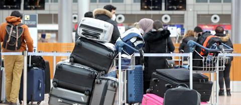 Passagiere warten mit viel Gepäck an einem Schalter im Hamburger Flughafen.
