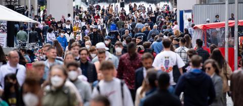 Viele Menschen spazieren durch die Fußgängerzone einer Innenstadt