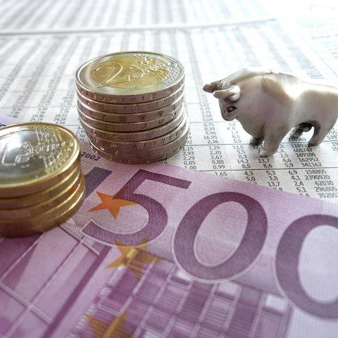 Sujet-Bild: Geld liegt auf einem Tisch. Eine kleine Bullenfigur steht daneben