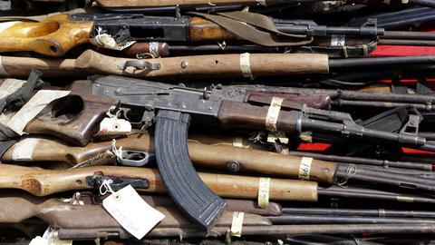 Mehrere Gewehre liegen auf einem Stapel