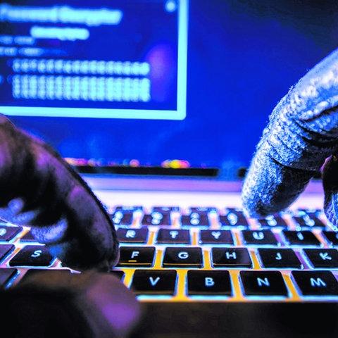 Zwei Hände (in Handschuhen) tippen vor einem Bildschirm auf eine Tastatur.