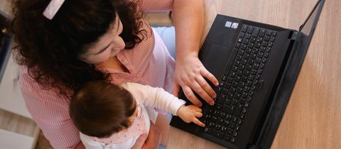 Eine Frau arbeitet am Laptop und hat ihr Kind auf dem Schoß (gestellte Szene).