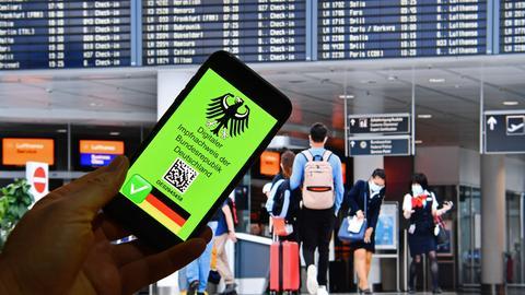 """Symbolbild: Auf einem Handydisplay am Flughafen steht: """"Digitaler Impfnachweis der Bunderepublik Deutschland"""""""