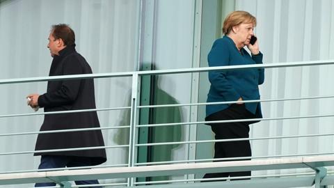 Angela Merkel steht auf dem Balkon des Kanzleramts und telefoniert. Links: CSU-Chef Alexander Dobrindt