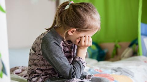 Ein Mädchen sitzt allein und traurig auf ihrem Bett.