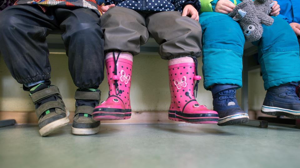 Kindergarten children dressed for a stay outdoors. You can only see their feet.