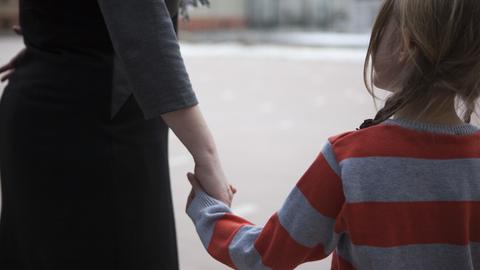 Eine Frau hält ein kleines Mädchen an der Hand