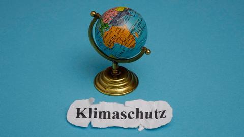 """Neben einem kleinen Globus steht das Wort """"Klimaschutz""""."""