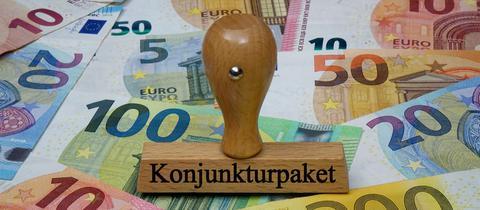 """Auf Geldscheinen steht ein Stempel, auf dem """"Konjunkturpaket"""" steht."""