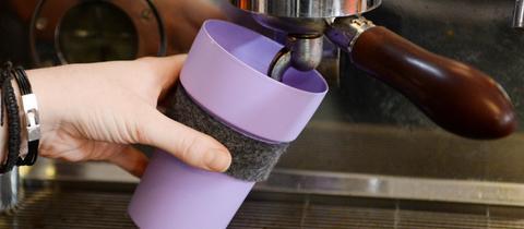 Kaffee läuft in einen Mehwegbecher