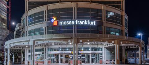 Der beleuchtete Haupteingang der Messe Frankfurt am Abend.