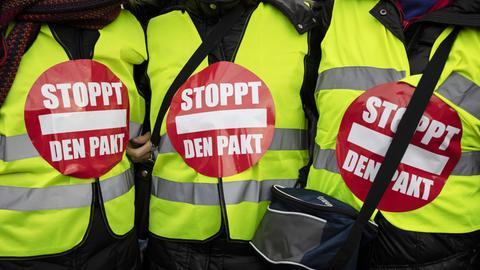 "Demonstranten mit Warnwesten, auf denen ""Stoppt den Pakt"" steht."