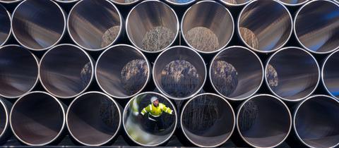 Ein Mitarbeiter prüft tonnenschwere Rohre für die geplante Gas-Pipeline.