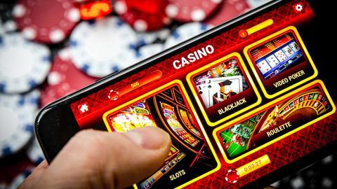 Symbolbild: Auf einem Handydisplay ist das Menü eines Online-Casinos zu sehen.